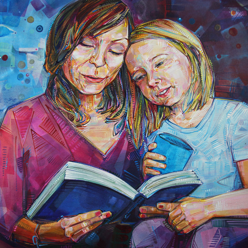 portrait of a white mother and daughter, the girl sitting in her mother's lap as they read together