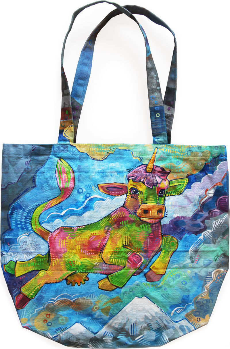 a canvas tote bag with a cow unicorn painted on it